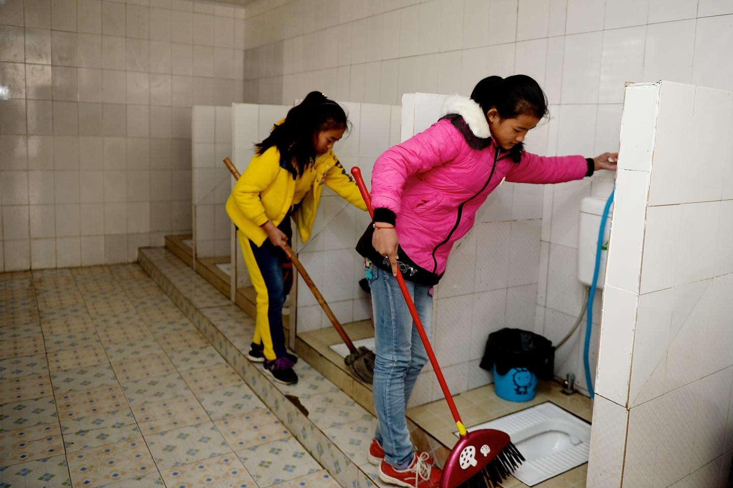 Two girls are tidying the toilet.