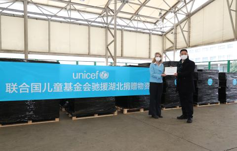 Cynthia McCaffrey, UNICEF Representative to China, presents a handover certificate to Xu Xingfeng, Deputy Commissioner of the Commissioner's Office in Shanghai under the Ministry of Commerce, at the cargo area of Pudong International Airport in Shanghai on 1 March 2020.