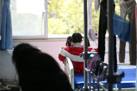 Five-year-old Yuanyuan* looks out the window of her room in a hospital affiliated to the Wuhan University of Science and Technology on 17 February 2020.