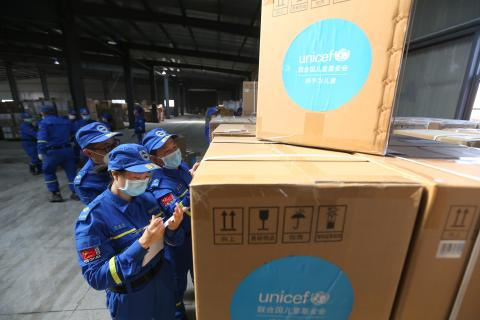 Volunteers check and accept UNICEF donated supplies in an emergency warehouse of the Hubei Charity Foundation in Wuhan, the epicenter of the COVID-19 outbreak, on 18 March 2020.