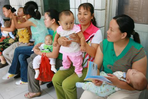 Mothers wait to have their children get health check at the Community Health Centre in Shibalidian of Beijing, one of the project sites supported by UNICEF and WHO, in 2007.
