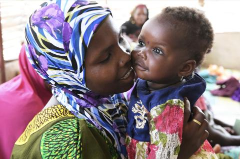 A woman is cuddling her baby after being vaccinated at the health center in a village in the center of Niger.