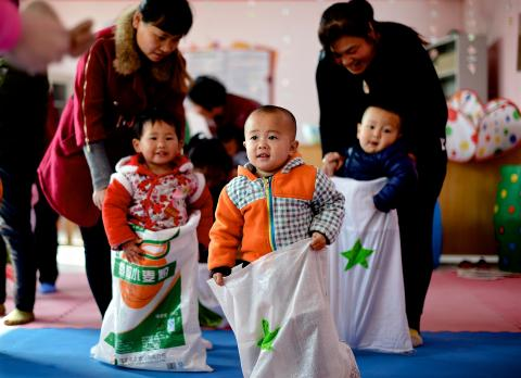 Young children join a game at a UNICEF-supported Integrated Early Childhood Development Centre in Fenxi County, Shanxi Province, in 2017.