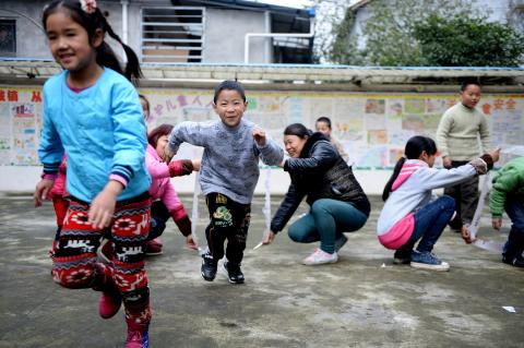 Boys and girls playing in school, China.
