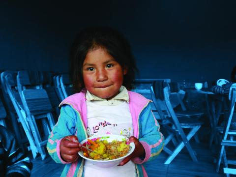 A girl eats lunch in the Hanaq Chuquibamba community in Peru.