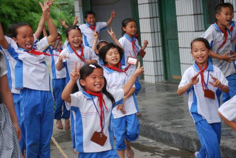 Children cheer for their victory in a tug-of-war game.