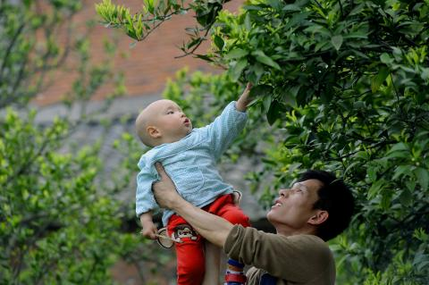 A father holds his child in Aijia Village, Hubei Province, in 2015.