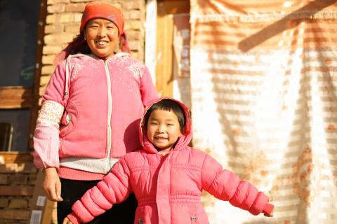 A girl and her caregiver at their home in Dingxi County, Gansu Province, in 2017.