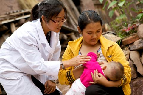 A woman breastfeeds her child under the guidance of a health worker in Wuding County, Yunnan Province, in 2011.