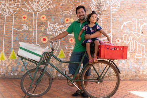Rafael Alfonso Araujo, 27, holds his daughter Selva, 2, atop the bicycle that serves as the family's transportation and mobile food-sales cart at the Torore center in Areguá, Central department, Paraguay, 28 January 2019.
