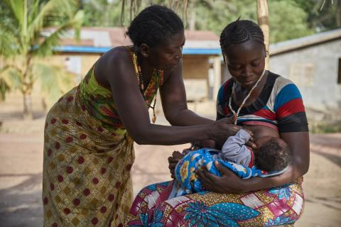 On 3 April, (right) Zainab Kamara, supported by her mother, breastfeeds one of her twin sons, 3-month-old Alhassan Cargo, in Karineh Village in Magbema Chiefdom, Kambia District.