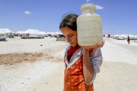 On 3 June 2017 in the makeshift camp at Ain Issa, 50 km north of the Raqqa in the Syrian Arab Republic, Horriya, 12, carries a jerrycan of water.