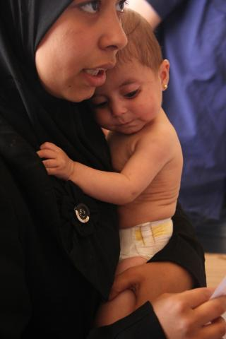 November 2014, Syria, a mother was holding her daughter who was receiving malnutrition treatment at a UNICEF supported clinic.