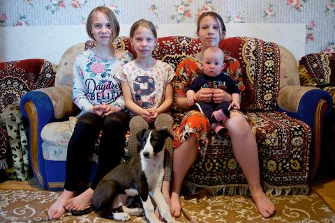 From left to right: Yana, 12, Lyubov, 10, Arina, 13 and Daniil, 7 months, sit in the living room of their small rented house in Nur-Sultan, Kazakhstan.