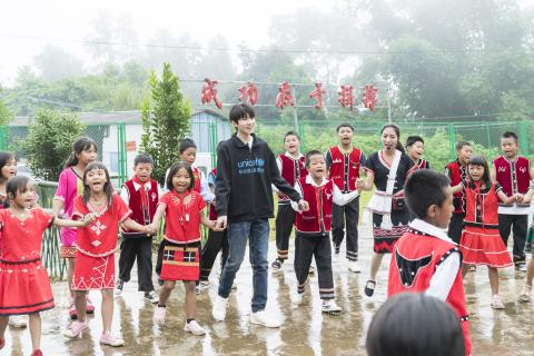 UNICEF Ambassador Wang Yuan dances with children from Wa ethnic group during his visit to Xinzhai Primary School in Cangyuan, Yunnan Province, where UNICEF is implementing a Social and Emotional Learning project, on 13th July, 2019.