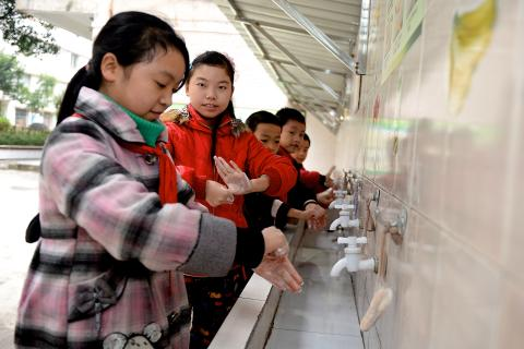 Children wash their hands at a primary school in Zhong County, Chongqing, in 2015.