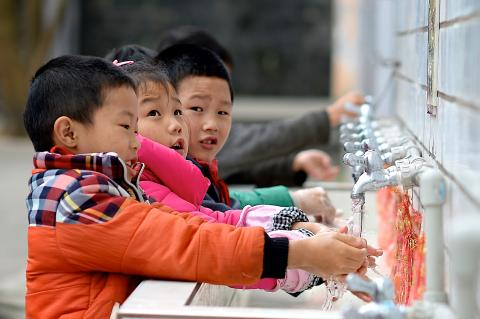 Children wash their hands at a school in Zhong County, Chongqing, in 2015.