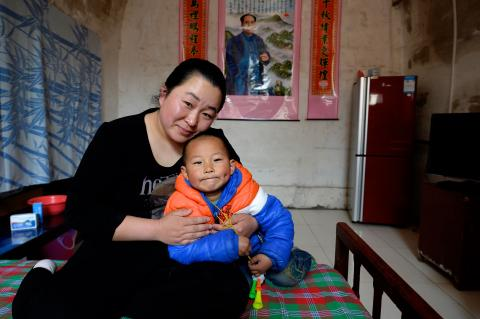A mother holds her child at their home in Fenxi Village, Shanxi Province, in 2017.