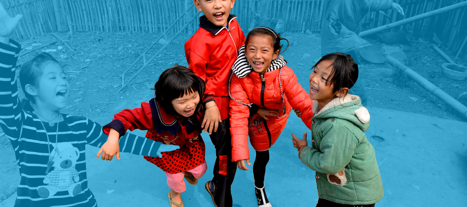 Girls and boys playing and laughing, rural China.