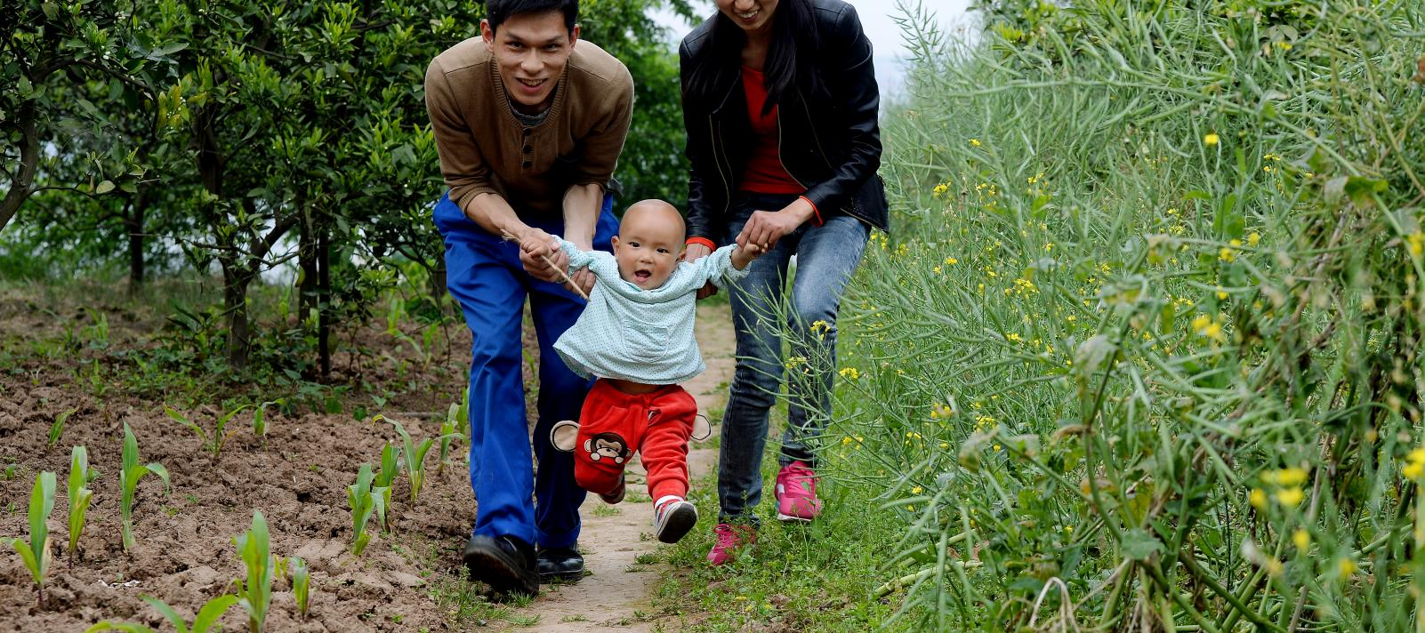 A child plays with his parents in Aijia Village, Yichang City, Hubei Province, in April 2015.
