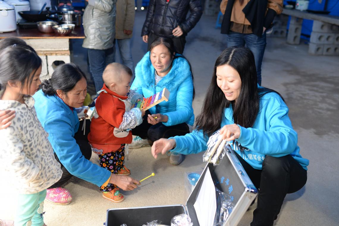 Wang Xiaolin (R1), Child Protection Officer at UNICEF China, introduces UNICEF's Early Childhood Development kit to villagers at a shelter in Ludian, Yunnan Province, following an earthquake in 2014.