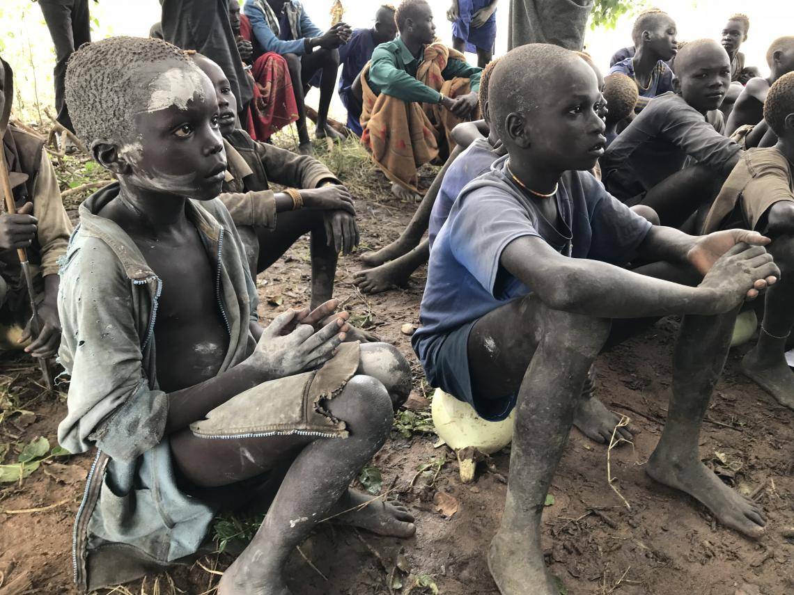 Boys living on the Ameth Magak Cattle Camp in the remote Lakes State in South Sudan attend the mobile school under a tree.