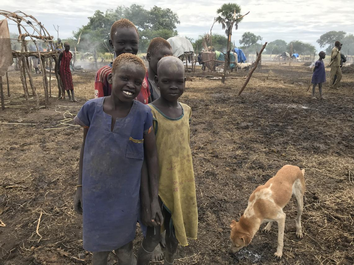 Children living on the Ameth Magak Cattle Camp in the remote Lakes State in South Sudan pose for pictures in front of their house.