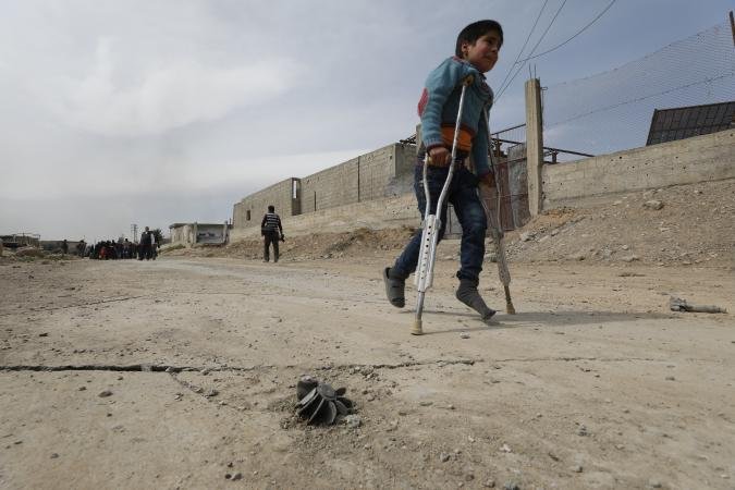 On 15 March 2018 in Beit Sawa, eastern Ghouta. a boy on crutches walks towards Hamourieh where an evacuation exit from eastern Ghouta has been opened.