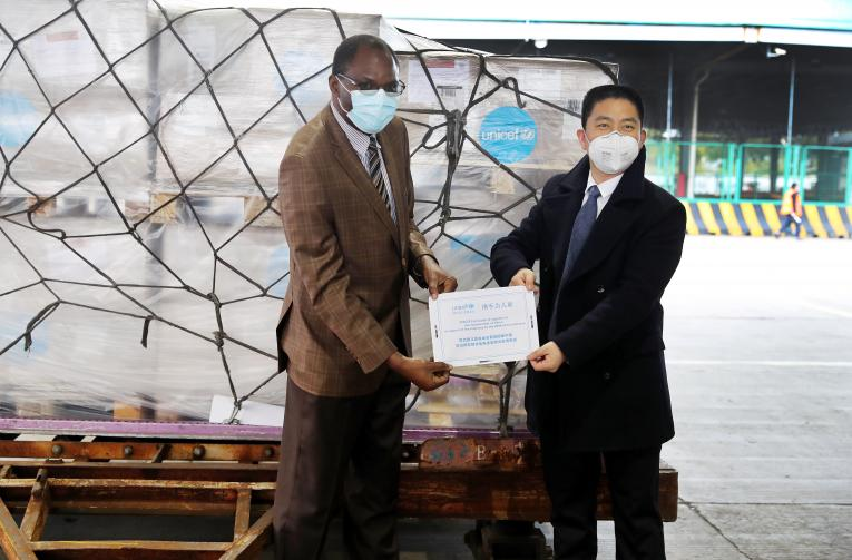 Jacob Mbeya, UNICEF Deputy Representative to China, presents a certificate of supplies to Xu Xingfeng, Deputy Commissioner of the Commissioner's Office in Shanghai under the Ministry of Commerce, at the cargo area of Pudong International Airport in Shanghai on 29 January 2020.