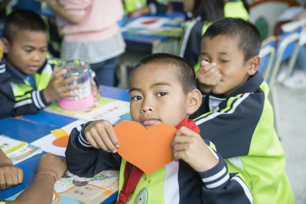 A boy holds a heart-shaped post-it during an social and emotional learning class at a school in Cangyuan, Yunnan Province, in July 2019.
